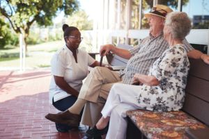 retired couples relaxing outside the house with a caregiver